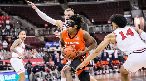 Illinois men's basketball player making his way to the basket past defenders during college basketball game